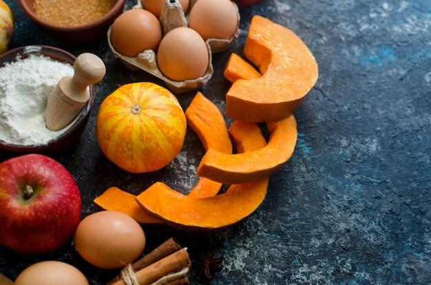 Concept de cuisson d'automne. cadre avec citrouille, pomme, noix, cannelle, oeuf et farine sur la table en bois.