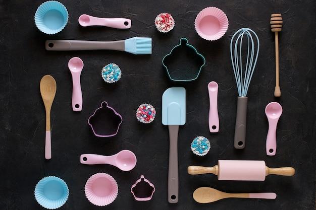 Concept de cuisson et de cuisson. modèle composé d'emporte-pièces, d'un fouet, d'un rouleau et d'outils de cuisson pour faire des bonbons. fond sombre. vue de dessus d'une nature morte de vacances