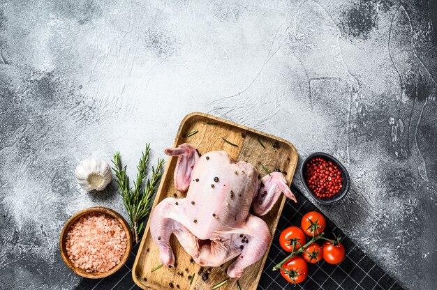 Concept de cuisson du poulet entier. ingrédients romarin, sel rose, ail et tomates cerises. vue de dessus.