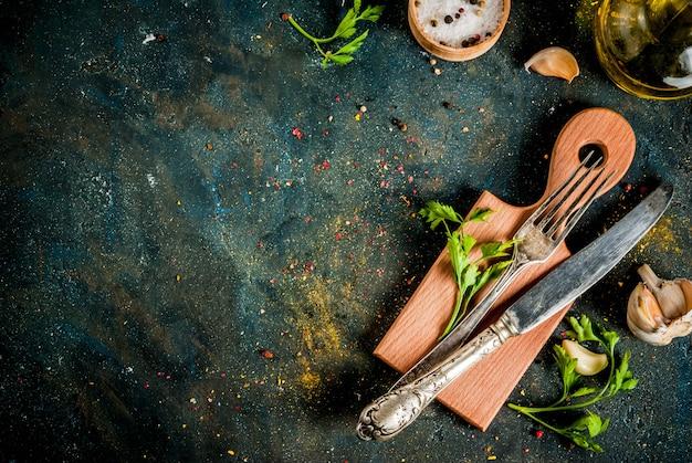Concept de cuisson, épices, herbes et huile pour préparer le dîner, avec planche à découper, couteau de table et fourchette, vue de dessus du fond