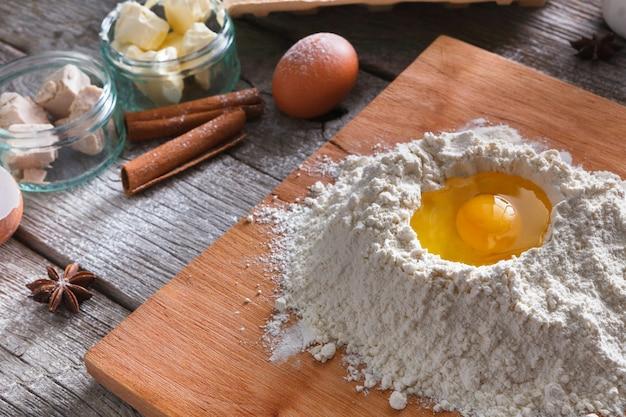 Concept de cuisson. farine et jaune d'oeuf à bord sur table en bois rustique, ingrédients de cuisine. faire de la pâte à levure sucrée