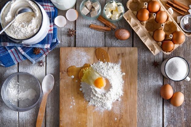 Concept de cuisson. farine et jaune d'oeuf à bord sur table en bois rustique avec des ingrédients pour la pâtisserie. faire de la pâte à levure sucrée, vue du dessus
