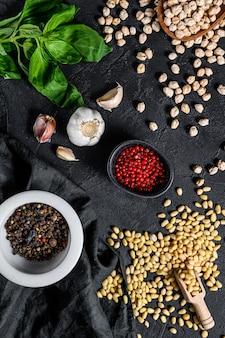 Concept de cuisson de l'humus. ingrédients: ail, pois chiches, pignons de pin, basilic, poivre.