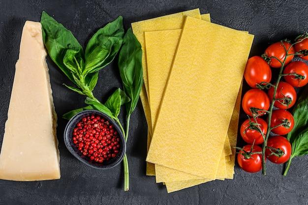 Le concept de cuisson des lasagnes. ingrédients, feuilles de lasagne, basilic, tomates cerises, parmesan, ail, poivre. vue de dessus