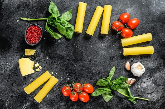 Le concept de cuisson des pâtes cannelloni. ingrédients basilic, tomates cerises, parmesan, ail. vue de dessus. espace copie
