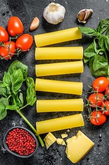 Le concept de cuisson des pâtes cannelloni. ingrédients basilic, tomates cerises, parmesan, ail. vue de dessus