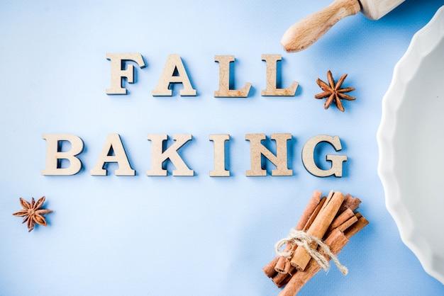 Concept de cuisson avec plat de cuisson blanc, rouleau à pâtisserie, épices pour la cuisson, sur un fond bleu clair, espace de copie vue de dessus