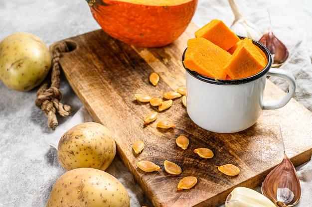 Le concept de la cuisson de la soupe de citrouille. morceaux de citrouille, pommes de terre, ail, graines de citrouille. soupe à la crème. . cuisine végétarienne