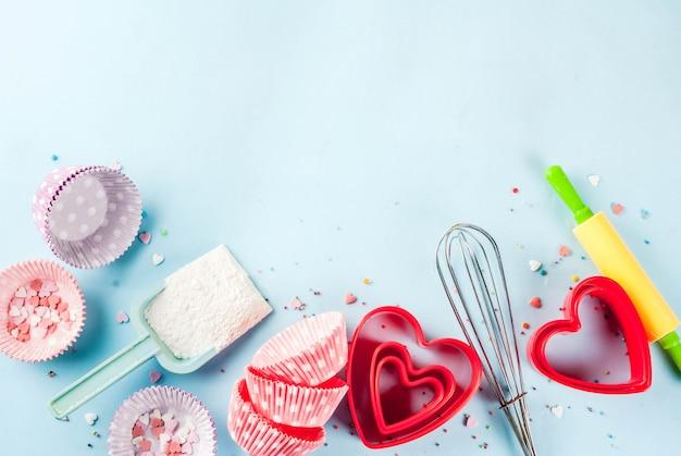 Concept de cuisson sucrée pour la saint-valentin, cuisine avec cuisson - avec un rouleau à pâtisserie, fouet pour fouetter, emporte-pièces, saupoudrage de sucre, farine. copyspace bleu clair, vue de dessus