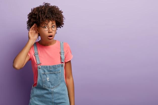 Concept de curiosité. une femme à la peau sombre impressionnée tente d'entendre les détails de la rumeur, tient la main près de l'oreille, écoute, porte des vêtements décontractés
