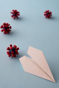 Concept de danger de mouche. avion en papier et modèles de virus covid-19