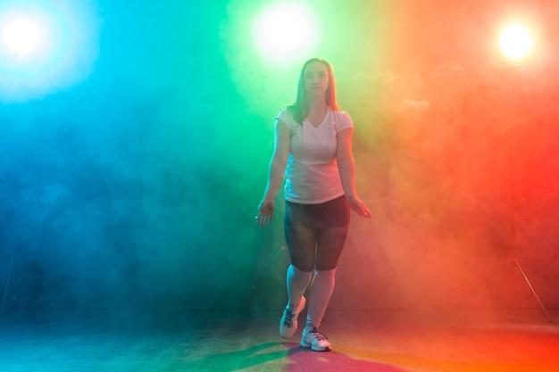 Concept de danse moderne, de sport et de personnes - jeune femme dansant du jazz funk dans l'obscurité sous une lumière colorée.