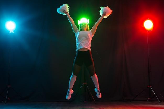 Concept de danse, de sport, de beauté et de personnes - une jeune pom-pom girl dans l'obscurité montre des pompons et sourit.