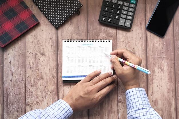 Concept de date limite avec la main de l'homme marquant la date sur la vue de dessus du calendrier.