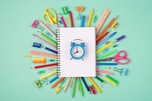 Concept de date limite de tâche ou de projet. haut au-dessus de la vue aérienne photo de papeterie multicolore et cahier vierge avec horloge bleue isolée sur fond turquoise