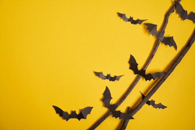 Concept de décoration halloween chauves-souris en papier noir branche sèche bâton fond carton jaune