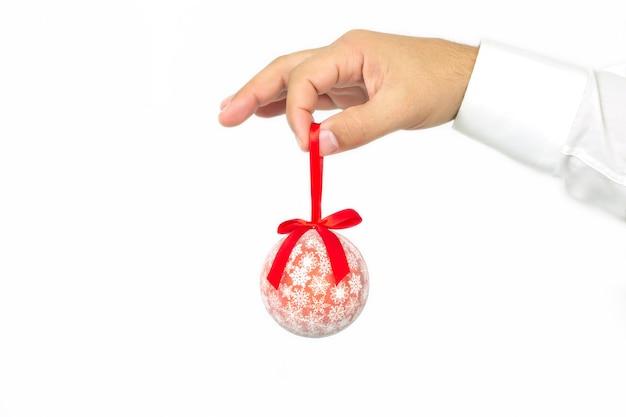 Concept de décoration et de personnes de noël, main d'homme tenant une boule de noël rouge isolé sur fond blanc