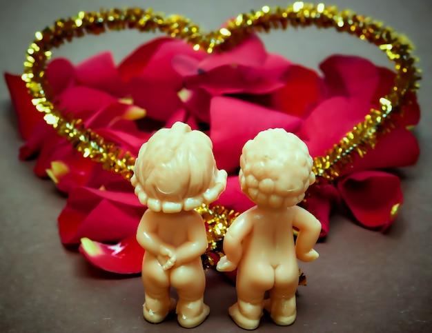 Concept de décoration de la saint-valentin-deux amateurs de poupées sur un fond avec des pétales de rose.
