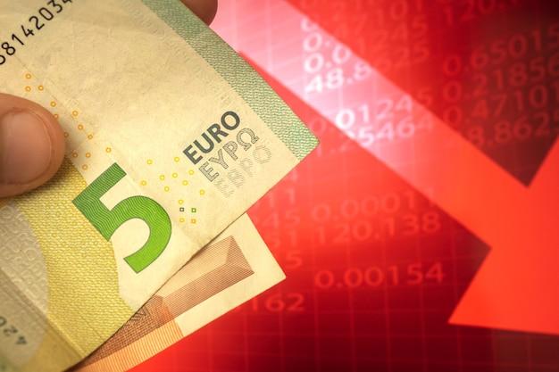 Concept décroissant d'argent en euros, billets en euros à la main, devise descendant sur fond de flèche rouge, finance et photo d'entreprise