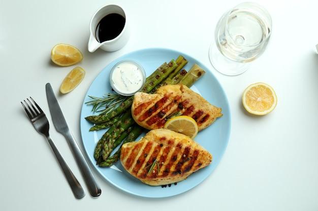 Concept de délicieux déjeuner avec poulet grillé et asperges sur fond blanc