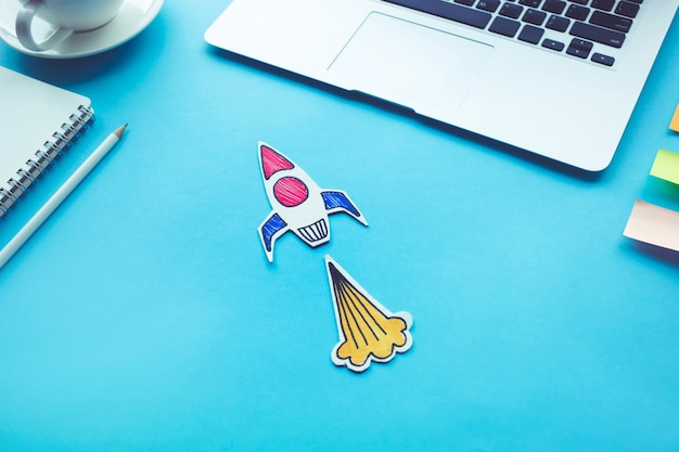 Concept de démarrage d'entreprise avec fusée sur la couleur de la table de bureau