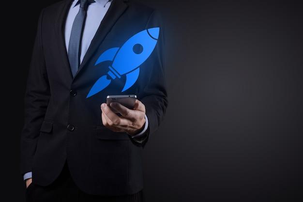Concept de démarrage avec un homme d'affaires tenant une icône de fusée numérique abstraite, la fusée lance et monte en flèche