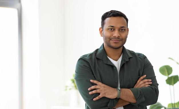 Concept de démarrage, jeune homme d'affaires indien prospère avec les bras croisés debout dans le bureau, souriant, regarde la caméra
