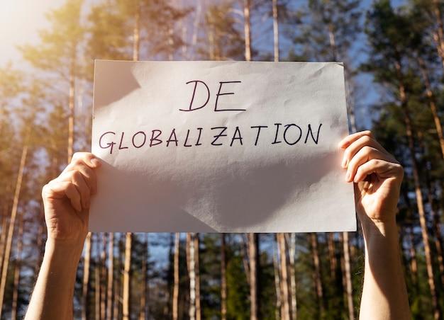 Concept de démondialisation et de mondialisation inversée. mot sur affiche papier dans les mains des hommes avec fond de forêt.