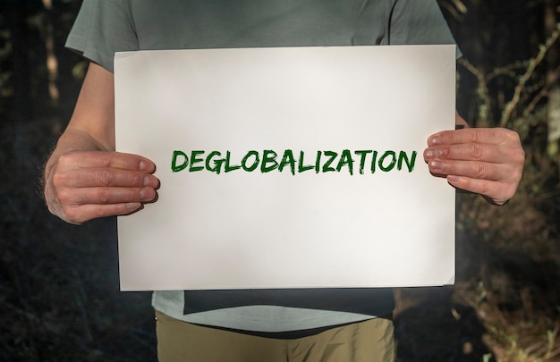Concept de démondialisation et de mondialisation inversée. mot sur papier placard dans les mains des hommes avec fond de forêt.