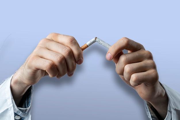 Le Concept De Dépendance Au Tabac, Arrêter Et Arrêter De Fumer De La Nicotine, Freiner à La Main Une Cigarette Isolée Photo Premium