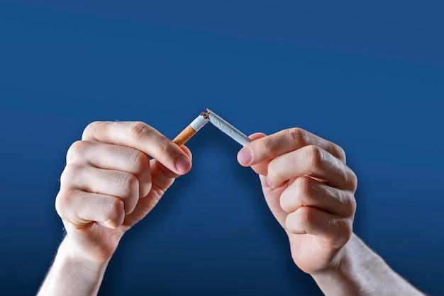 Le concept de dépendance au tabac, arrêter et arrêter de fumer de la nicotine, freiner à la main une cigarette isolée