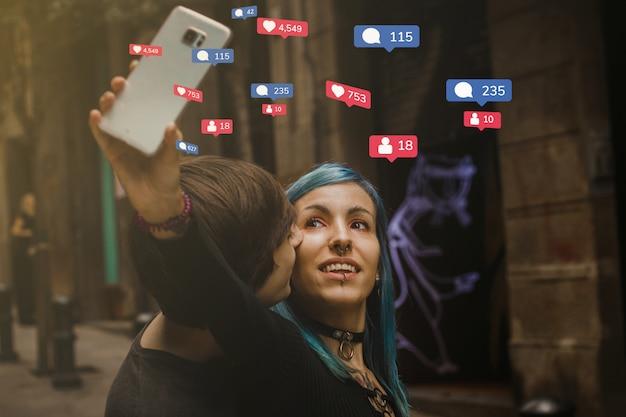 Concept de dépendance aux médias sociaux: un couple de milléniaux prenant des photos avec le smartphone dans une rue, mode de vie des adolescents