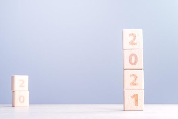 Concept de design abstrait de nouvel an 2021 - cubes de bloc de bois numéro isolés sur table en bois et fond bleu brouillard léger.