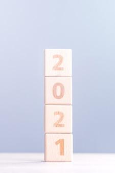 Concept de design abstrait de nouvel an 2021 - cubes de bloc de bois numéro isolés sur table en bois et fond bleu brouillard léger