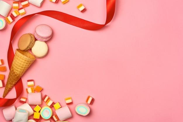 Concept de design d'arrière-plan de fête d'anniversaire : bonbons, glaces aux fleurs, beignets et biscuits sur le fond en bois blanc avec espace de copie ; vue de dessus, mise à plat