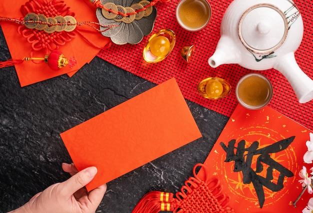 Concept de design du nouvel an lunaire chinois de janvier - femme tenant, donnant des enveloppes rouges (ang pow, hong bao) pour de l'argent chanceux, vue de dessus, mise à plat, frais généraux ci-dessus. le mot «chun» signifie le printemps à venir.