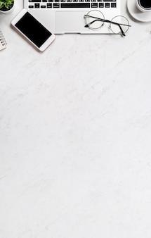Concept de design financier d'entreprise, table de bureau en marbre blanc vue de dessus de bureau avec téléphone intelligent, carte de crédit maquette, pièces de monnaie, ordinateur portable, mise à plat, espace de copie