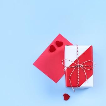 Concept de design de la saint-valentin - boîte-cadeau enveloppé rouge, blanc isolé sur fond de couleur bleu clair