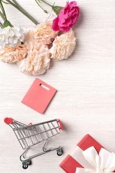 Concept de design de voeux de fête des mères avec fleur d'oeillet, idée de cadeau de vacances et panier sur fond en bois.