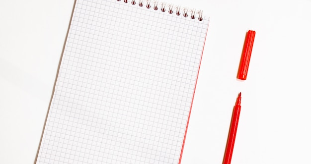 Concept de design - vue de dessus du cahier à spirale rouge et collection de crayons de couleur isolé sur fond blanc