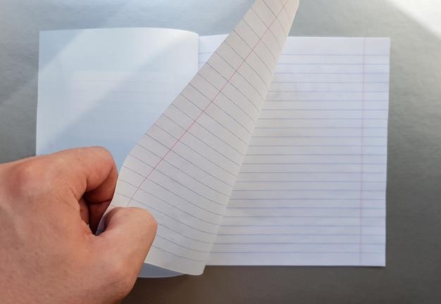 Concept de design - vue de dessus d'une main masculine de haute qualité feuilletant une feuille de cahier à rayures bleues. vue de dessus, espace de copie, mise à plat.