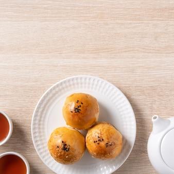 Concept de design vue de dessus de la pâtisserie jaune de gâteau de lune, gâteau de lune pour les vacances de la fête de la mi-automne sur fond de table en bois