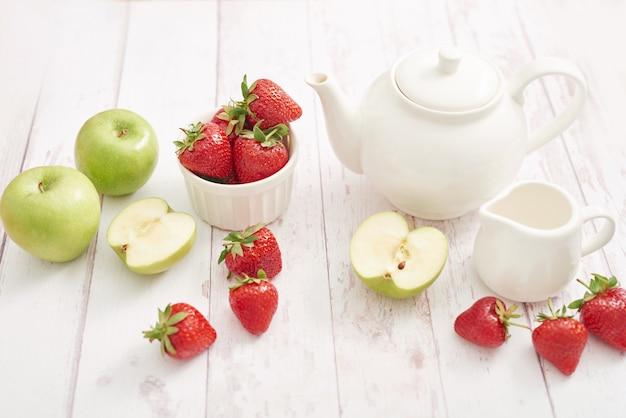 Concept de désintoxication. fruits et baies savoureux. nourriture saine. véganisme, végétarisme, alimentation crue. fraises et pommes. fruits frais d'été. copiez l'espace. vitamines dans les aliments. petit-déjeuner sain. service à thé