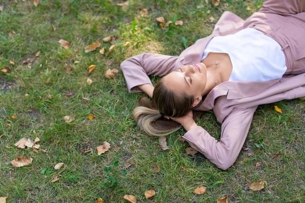 Concept de désintoxication numérique jeune femme pensive se trouve dans le parc sur l'herbe avec les yeux fermés agrandi à...