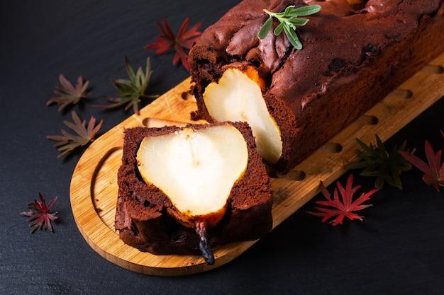 Concept de dessert alimentaire fait maison gâteau au chocolat rustique ou brownie et gâteau aux poires sur une ardoise noire avec espace de copie
