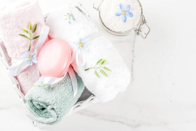 Concept détente et bain spa, sel de mer, savon, avec cosmétiques et serviettes dans la salle de bain