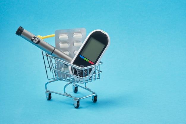 Concept de diabète. fournitures pour diabétiques en chariot, pilules, glucomètre, stylo seringue à insuline sur fond bleu