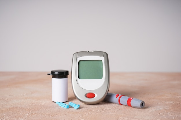 Concept de diabète avec lecteur de glycémie numérique et stylo lancette