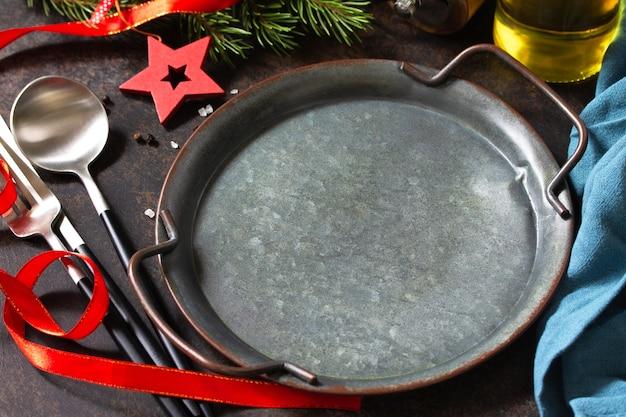 Concept de dîner de noël, arrière-plan culinaire. assiette, couverts et serviette en métal sur des comptoirs en pierre. table dressée sur un plan de travail en pierre.