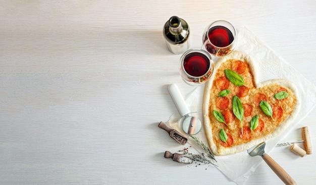 Concept de dîner romantique pour deux avec vin rouge et pizza en forme de coeur. dîner pour la saint valentin